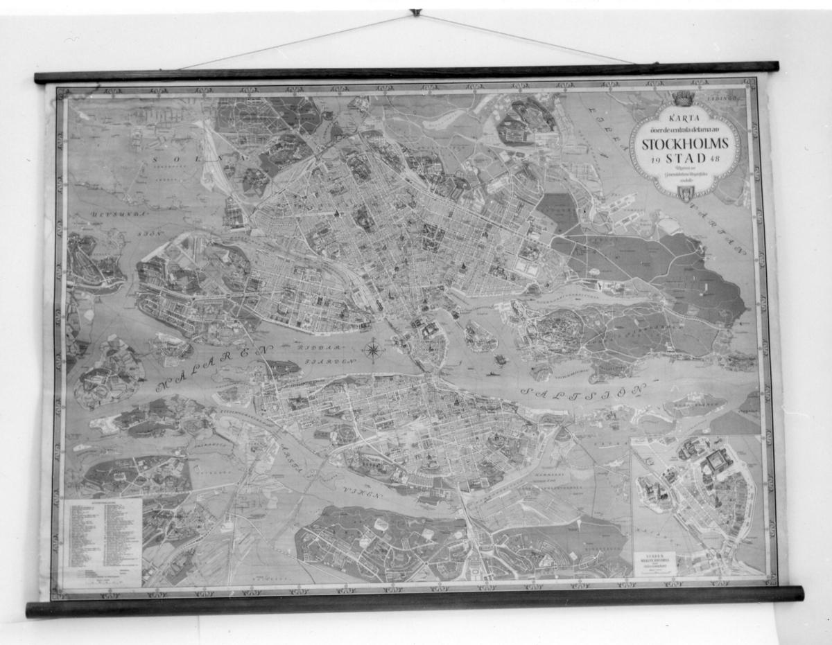 Stadskarta över Stockholm från år 1948, med en inflikaddetaljkarta över Gamla Stan. Kartan tryckt på papper på väv. Påkartans långsidor är träribbor fästade. Vid den övre är ett snörefäst, för upphängning på vägg.