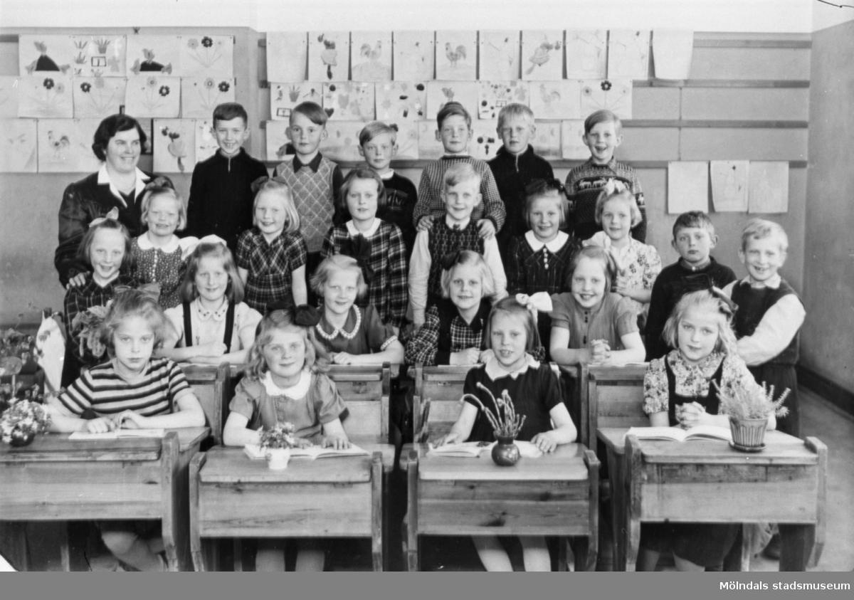 Fröken R. Sylvén med elever. Flickor sittandes i bänkar. Flickor och pojkar ståendes bakom. 1:a klass.Teckningar på väggen. Med på bilden finns sittande till höger Berit Gustafsson,  född Larsson 1936. Kvarnbyskolan kallades vid den här tiden för Centralskolan.