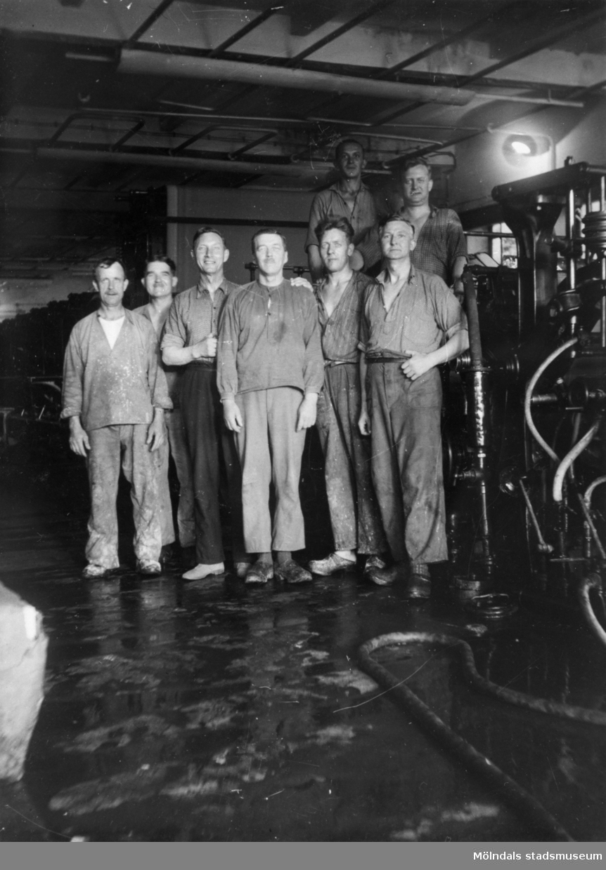 Pappersarbetare står uppställda framför en maskin i Papyrusfabriken. 1930-tal.