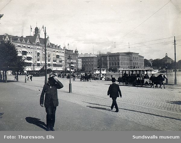 Vy från Kungsträdgården mot Strömkajen. I förgrunden en hästdragen spårvagn och i bakgrunden Grand Hotel och Nationalmuseum.