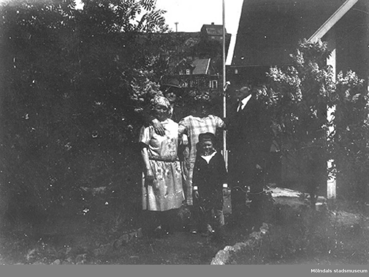Toltorpdalen i Mölndal. Två kvinnor och en man samt ett barn stående i en trädgård.
