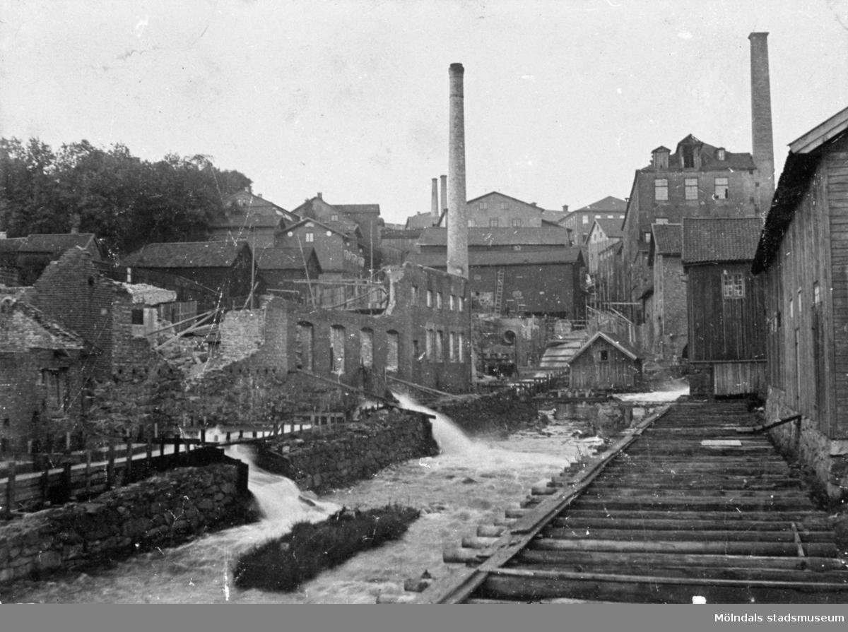 Nedre delen av forsen (Mölndalsfallen) sommaren 1894. Uppströms ses Forsebron och kvarnrännan.I förgrunden till vänster ses ruinerna efter Delbancos fabrik som brann sommaren 1894.
