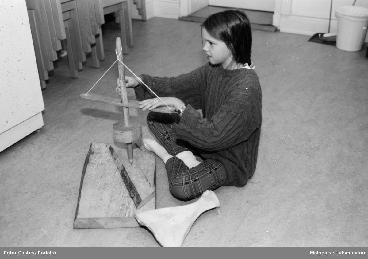 Ett barn sitter på golvet och snurrar på ett träföremål. Utställningsvernissage av och om Katrinebergs daghem på Mölndals museum 1993-09-10.
