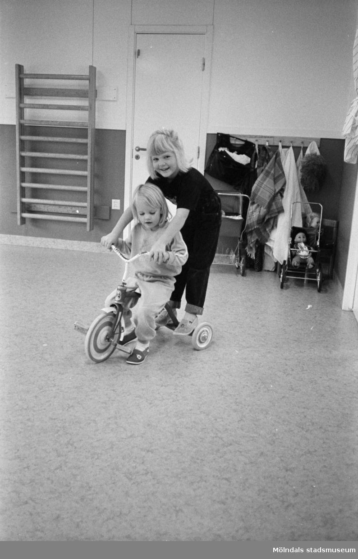 Två barn som sitter alternativt står på en trehjuling inomhus på Katrinebergs daghem. I bakgrunden ser man en ribbstege av trä uppsatt på väggen, några dockvagnar och filtar.