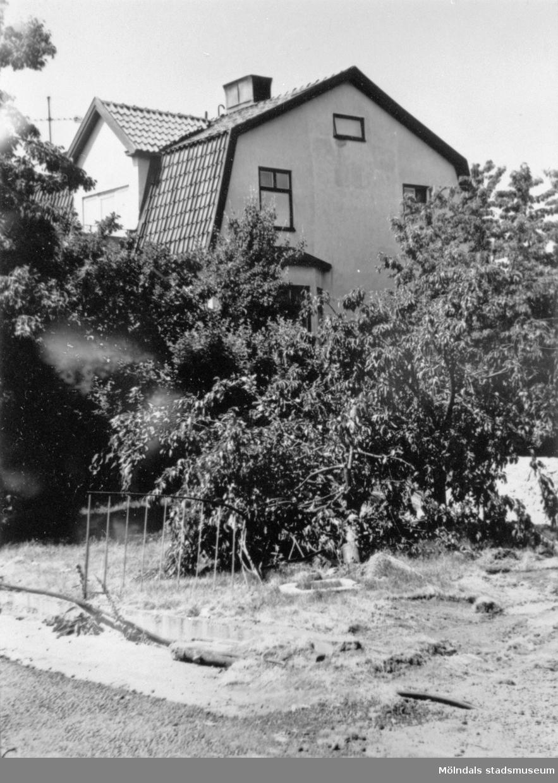 Rivning av området kring Mölndalsbro-bygget 1975. Man ser Ahlbergs skrädderi (Barnhemsgatan 16) från sydost, skymt av grönska.