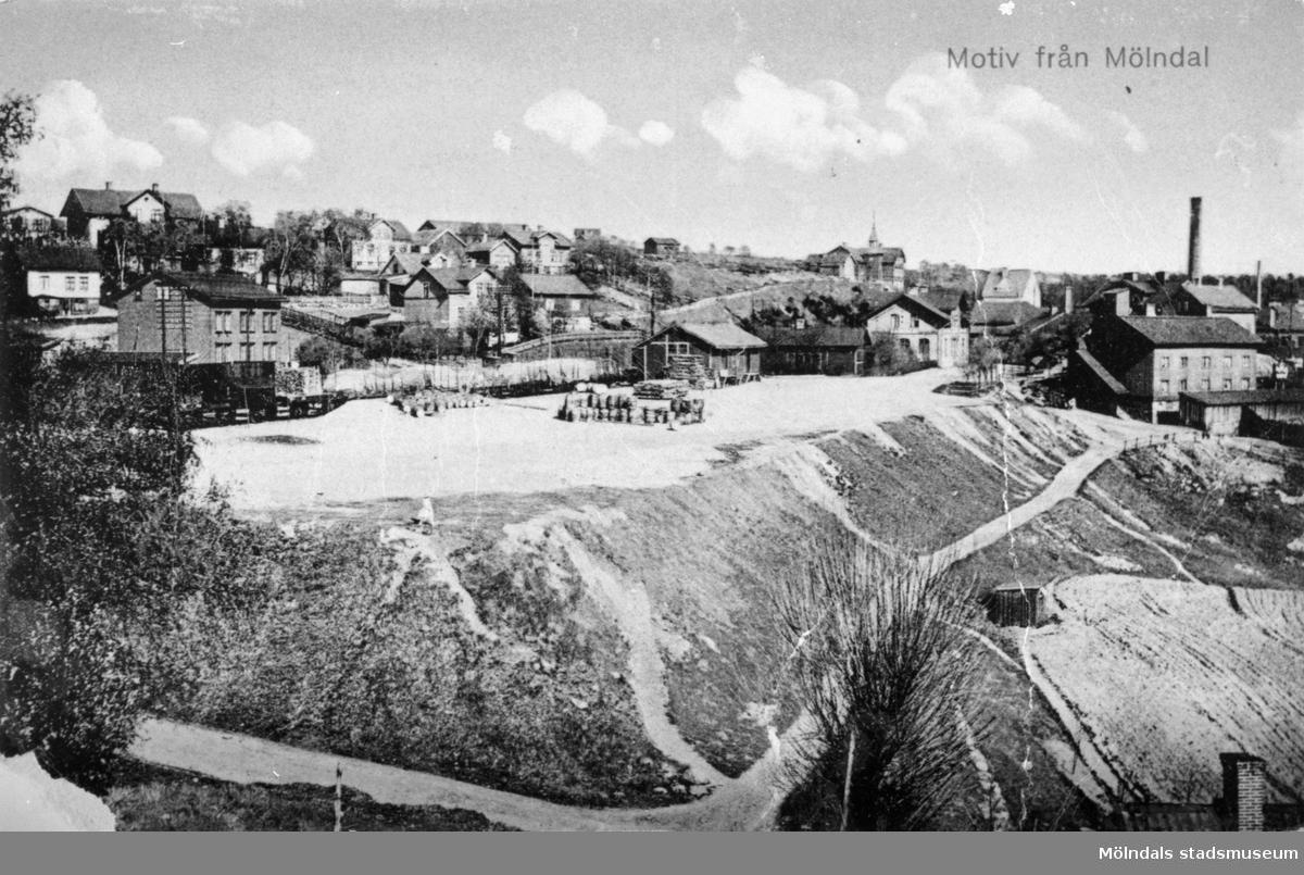 """Vykort """"Motiv från Mölndal"""" med utsikt från sydväst (något hus vid Samuel Norbergsgatan) mot Mölndals Övre Järnvägsstation och Stensjöbacke. Längst upp till vänster ses Ormås skola. Huset med torn, längst upp till höger, är Hemmet (Ormåsgatan 4) som uppfördes 1909 och brann 1917. // Lars Gahrn"""
