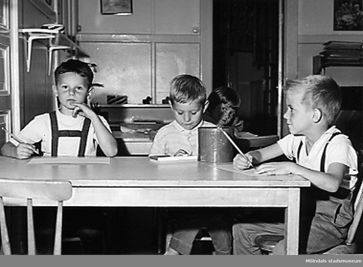 Några barn som sitter och ritar vid Holtermanska daghemmet 1953.