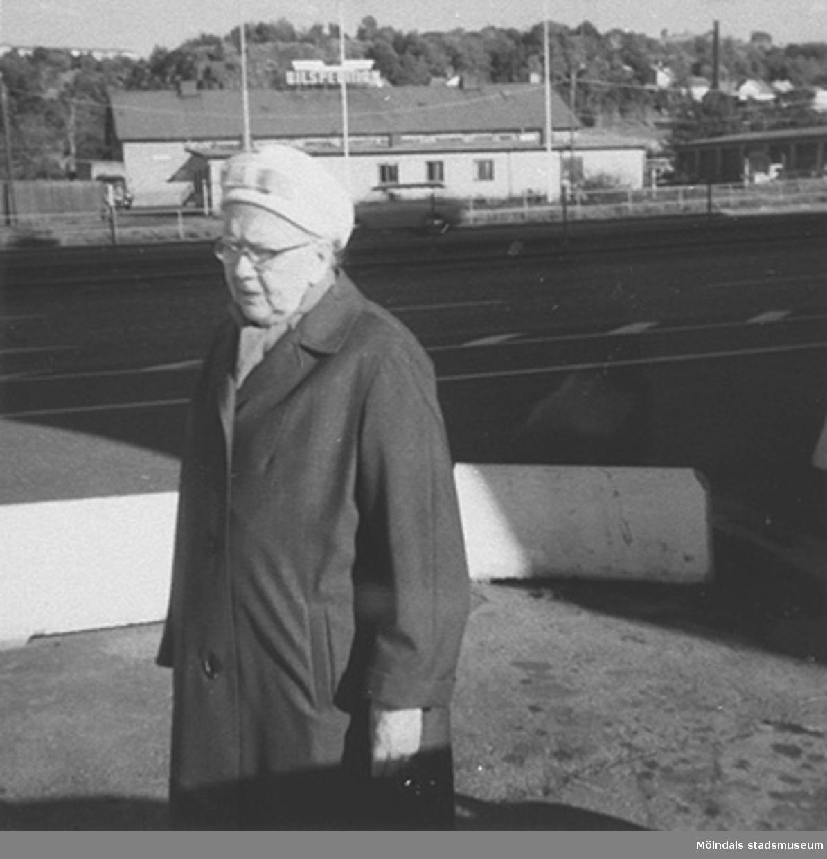 En okänd dam, iklädd hatt och kappa, går på en gata i Mölndalsbro, 1960-tal. I bakgrunden skymtar Bilspedition.