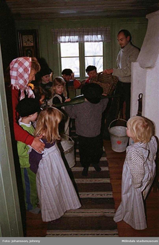 Museipedagog Håkan Strömberg visar förskolebarn Olas stuga 1999-02-18. Tema: Livet förr.