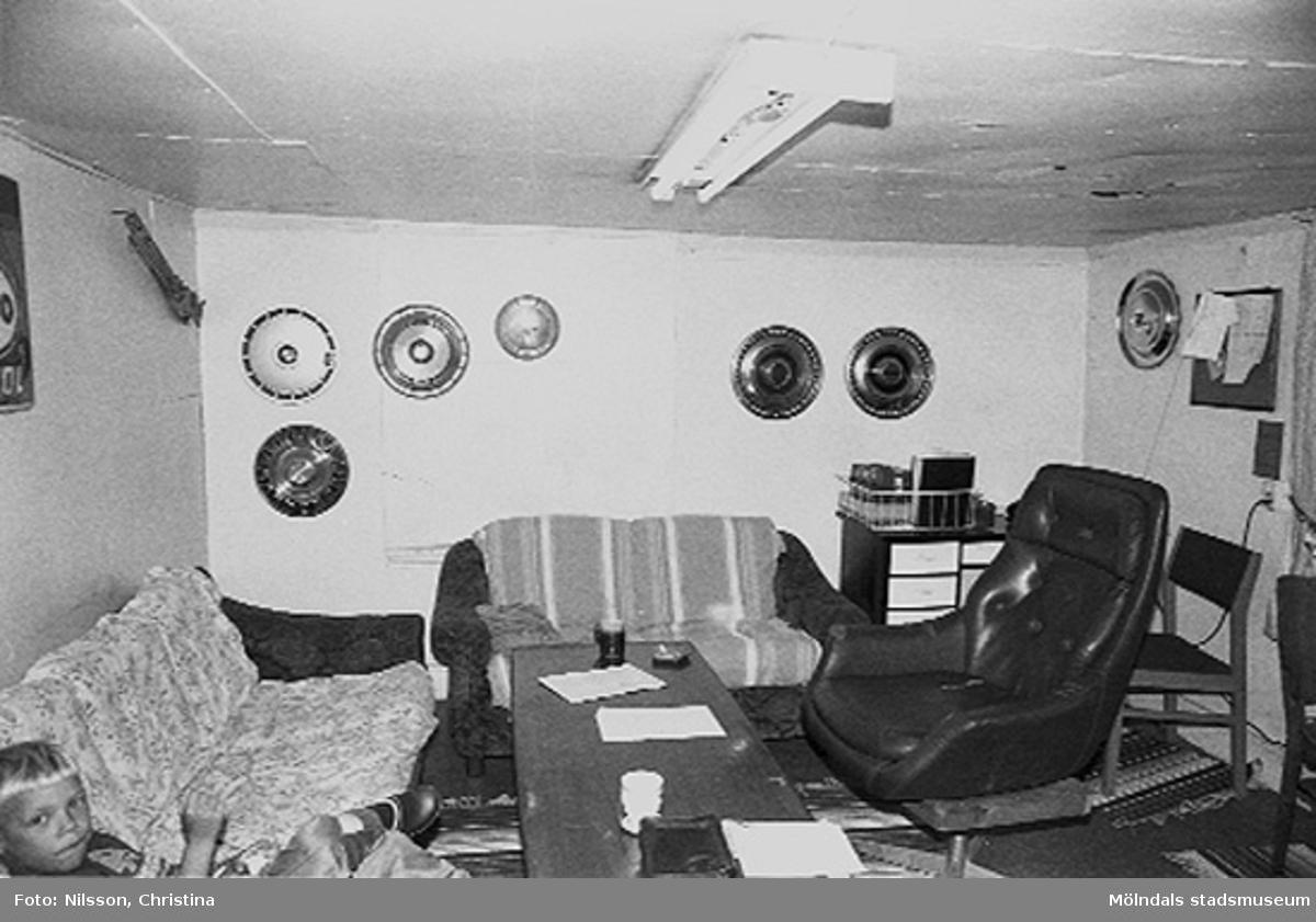 Interiör från undervåningen i ett rum. Takhöjden är ca 180 cm. Rakt fram i bild har ett fönster igenbommats i söder. Fönsterbrädan skymtar till vänster om soffan. Lokalen nyttjades på 1990-talet som fikarum för de som hade hobbyverkstäder i f.d. spinneriet. En okänd pojke sitter i vänstra hörnet.