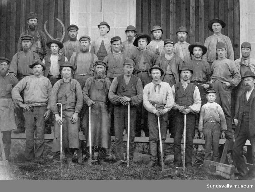 """Arbetare vid Ortvikens sågverk, ena skiftet. 2 vakter (dag- och nattsågningsskift). Mannen som står längst ner till höger i knallhatt och helskägg är faktor. Männen i främste ledet håller s k """"rushakar"""" som användes för styrning av stockarna till sågramarna."""