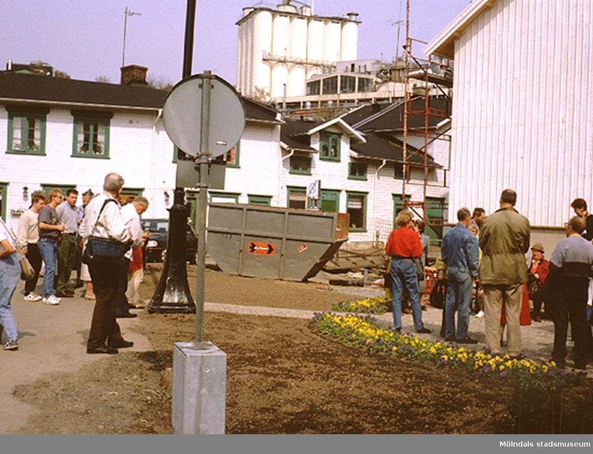Folksamling vid Lyktplatsen i Kvarnbyn. Gatlyktan invigs på Kvarnbydagen 25/4 1993. Det vita huset rakt fram är Kråkans Krog och till höger ligger Korndal 2. I bakgrunden ses Soabs silotorn på höjden.
