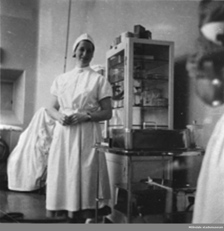 """Undersköterska Syster Barbro, på operation 1 vid Sabbatsbergs sjukhus i Stockholm, cirka 1958. Dagarna brukade börja kl. 06.30. Slutade när de olika dukarna och instrumenten var torkade och räknade. Ofta omkring 22.00!Vid 18 års ålder fick man börja på Svenska Röda Korsets sjuksköterskeutbildning. Då blev eleven antagen till 3 månaders provtjänstgöring den s.k """"plättperioden"""". Under denna tid användes en liten mössa till arbetsuniformen som man fick vid utbildningens början. Den lilla mössan avvek från den ordinarie mössan för att visa att eleven gick på prov. Efter provtjänstgöringen fick eleven veta om hon godkändes för vidare utbildning på 3,5år. Efter 2 års studier fick eleven bära den vita armbindeln och blev därmed undersköterska.Arbetsuniformen var skräddarsydd och bestod av en blå bomullsklänning, ett vitt förkläde som knäpptes i kors i linningen med särskilda manschettknappar och en vit mössa. Klänningens längd skulle vara ett visst antal centimeter ovanför golvet och förklädet skulle vara ett visst antal centrimeter ovanför den nedersta klänningsfållen. Man fick endast använda svarta strumpor och svarta skor eller bruna strumpor och bruna skor till klänningen.Till klänningen hörde också en vit krage till som fastsattes med knapp baktill och  med sjuksköterskebroschen framtill. Till klänningen fanns ett särskilt bälte som gjorde att förklädet inte skulle vika sig i midjan. På vänster ärm fastsattes den vita armbindeln som visade att det var en Röda Kors syster! Den vita mössan var enligt ett mönster särskilt för Röda Korsets sjuksköterskor (varje sjuksköterskeskola hade sin egna design av mössan). Endast nålar med pärlhuvud fick användas på mössan. På mössan fästes hakrosetten. Vid utomhusvistelse fick man bära den tillhörande svarta kappan. Den skulle vara längre än klänningen. Till kappan var man tvungen att använda svarta strumpor och svarta skor och sätta fast den vita armbindeln på vänster ärm. Man använde också en särskild mössa med hakband den s.k Ka"""