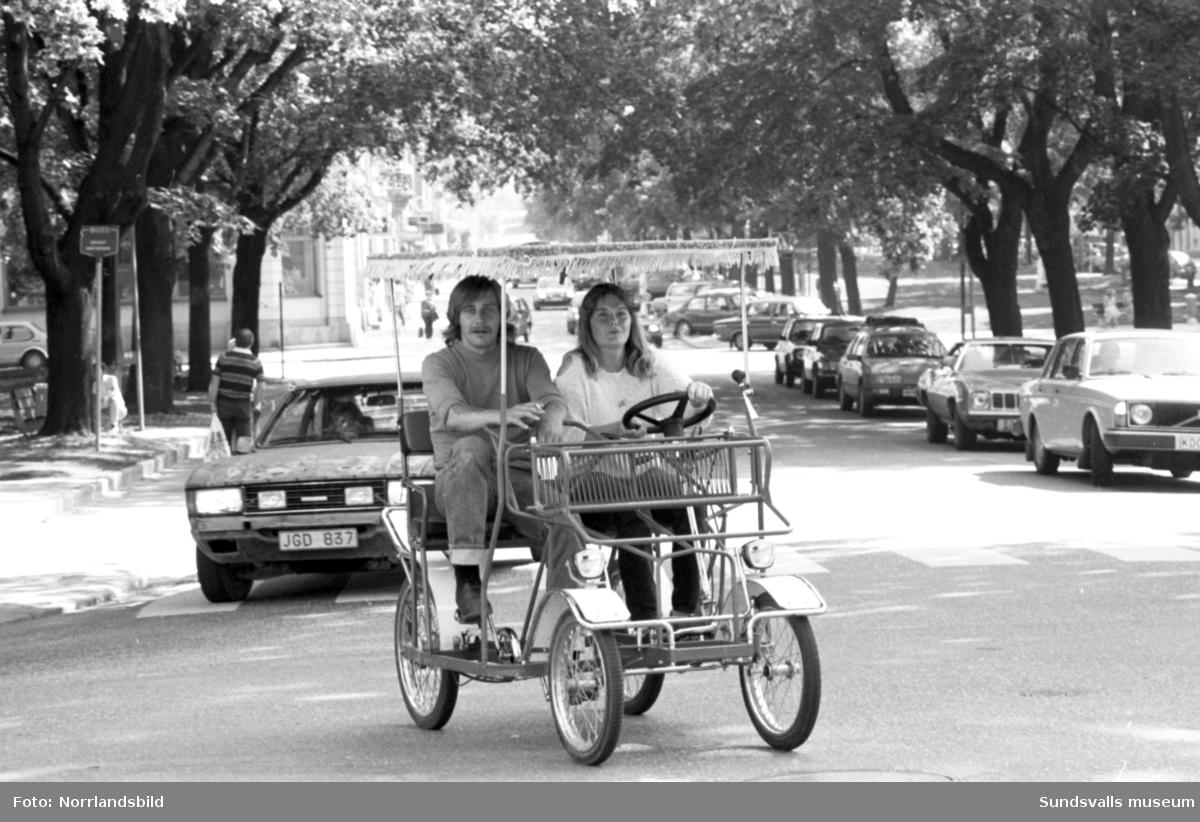 """""""Cykelbil."""" Ett ungt par framför en slags fyrhjulig cykel med tak och ratt på Esplanaden."""