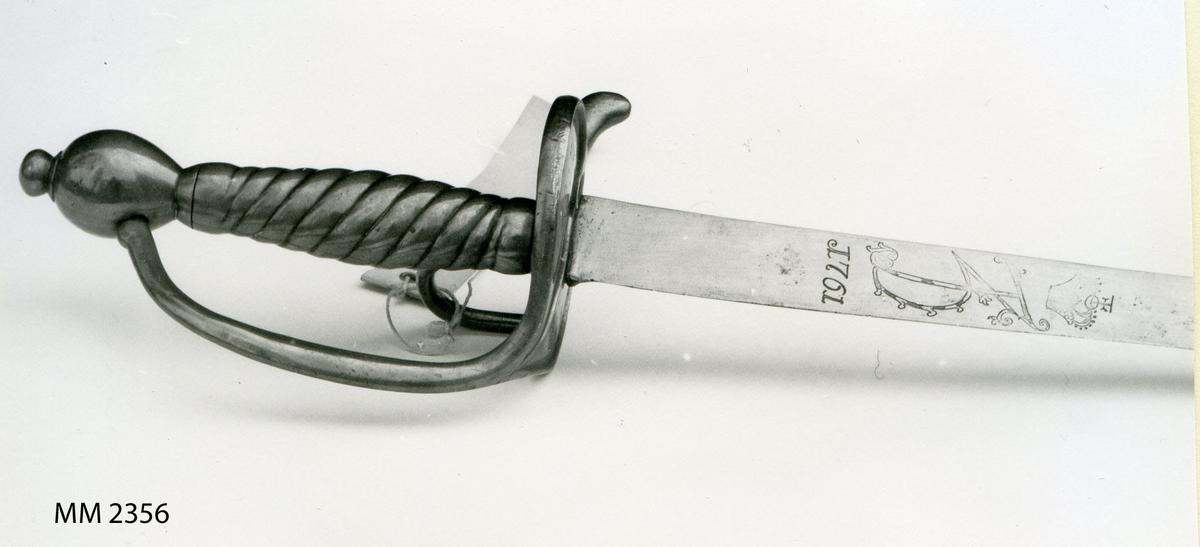 Sabel (som närmast liknar en huggare) från 1761. Klinga i stål med Frederik V namnchiffer. Handtag och parerskiva i mässing. Parerskivan hjärtformad.