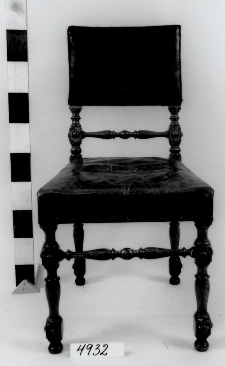 Stol av trä, fernissad. Svarvade ben och tvärslå. Ryggståndare och tvärslå i ryggen svarvade. Rektangulärt ryggstöd samt sits klädda med skinn. Från senare delen av 1800-talet.