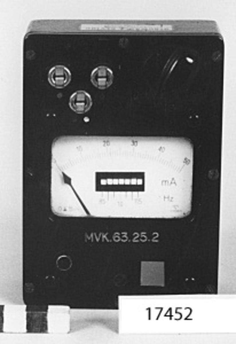 Frekvensmätare monterad i kåpa av svartmålat trä. Framsidan av svart bakelit? I mitten fönster visande skala graderad 0-50 m A samt sensorer med skala 8,5-11,5 Hz. Överst tre kabeluttag samt en ratt. Märkt med gul etikett: Bergman & Beving Aktiebolag Stockholm, samt MVK.63.25.2 (63=1963)