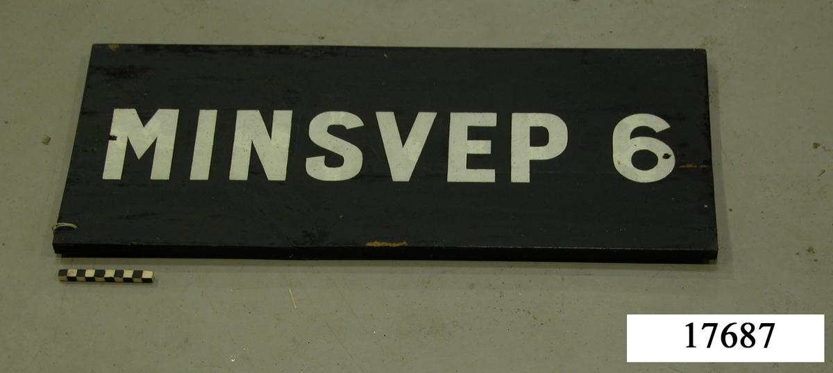 """Rektangulär skylt, framsidan svartmålad, hål för upphängning. Vit schablonmålad text: """" MINSVEP 6"""", övermålad text."""