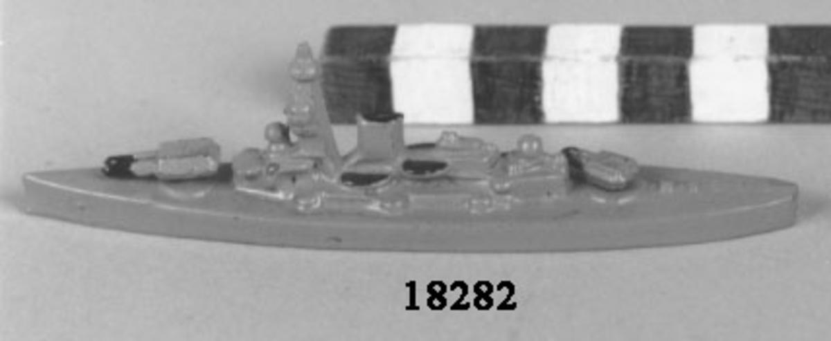 Fartygsmodell i form av pansarskeppet Gustav V gjuten av metall i ett stycke, målad i grått. Plan botten. Artilleripjäser i för och akter, dubbla vridbara. Mast och livbåtar med svart kapell, fyra stycken.