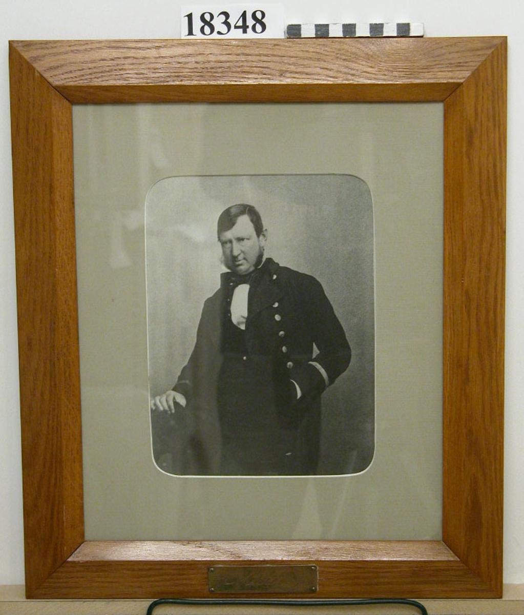 """Fotografi inom glas och ram föreställande B.J. Adelborg. Man sittande på stol klädd i uniform. Passepartout  B = ca 50 mm. Ram av ljus ek fernissad, profilerad. Nederst mässingsbricka med graverat namn efter namnteckning: """"B.J. Adelborg"""". Baksida kartong försedd med text: """" B.J Adelborg född d. död d. CADK 1858-63 """". Neg.nr A 376 4:25"""