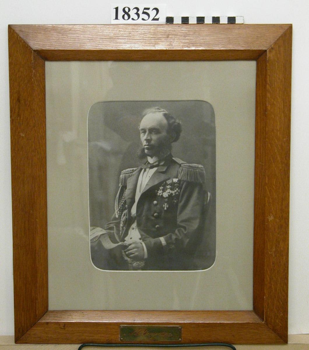 """Fotografi inom glas och ram föreställande C.C. Engström. Man sittande i stol klädd i paraduniform med medaljer, hållande båthatt. Tunt hår och breda polisonger. Passepartout  B = ca 50 mm. Ram av ljus ek fernissad, profilerad. Nederst mässingsbricka med graverat namn efter namnteckning: """" C.C Engstöm """". Baksida kartong försedd med lapp: A Carl Christian Engström född 1827 19/6 död 1916 22/4 chef 1876-78 Neg.nr A 376 6:17"""