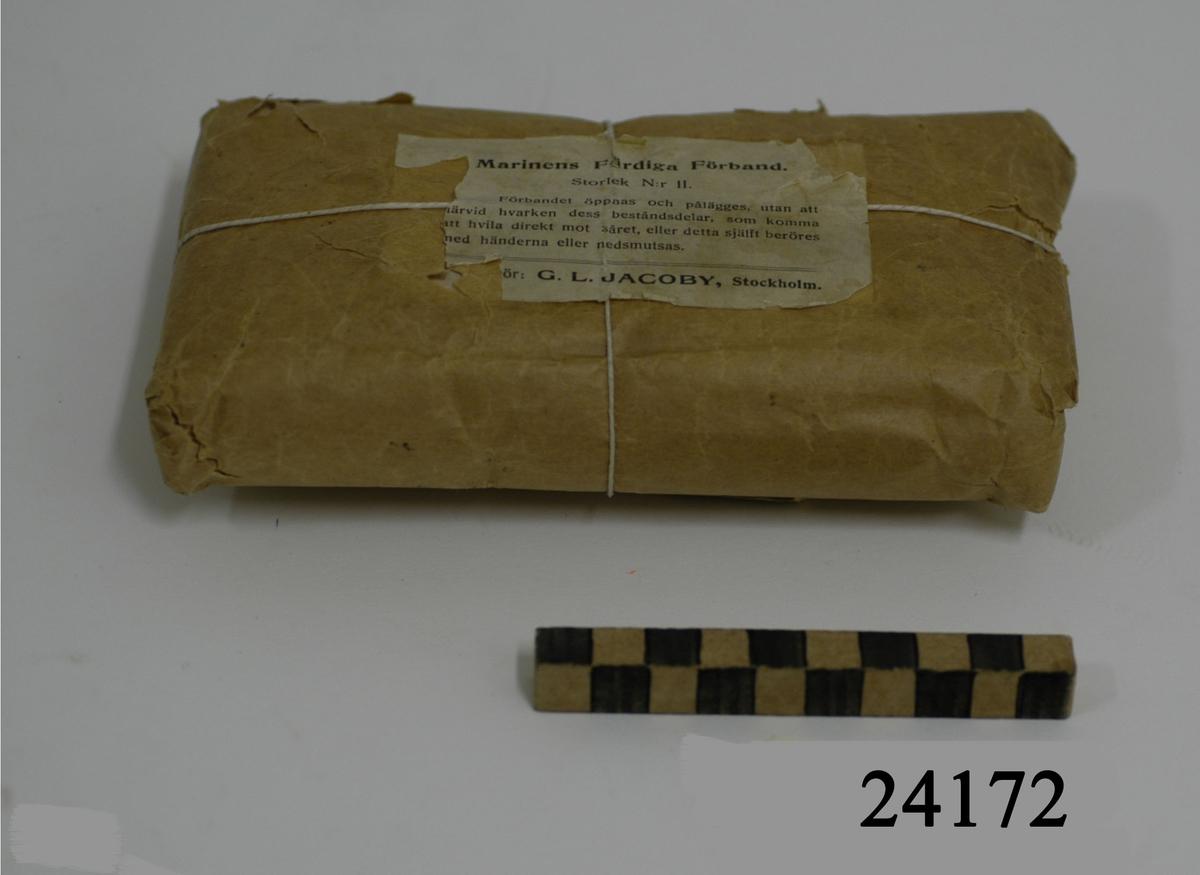 """Rektangulär förpackning av brunt paketpapper. Omknutet av tunnt vitt snöre. Påklistrad vit etikett på förpackningens framsida med följande text: """"Marinens Färdiga Förband. Storlek N:r II. Förbandet öppnas och pålägges, utan att därvid hvarken dess beståndsdelar, som komma att hvila direkt mot såret, eller detta själft beröres med händerna eller nedsmutsas. G.L.JACOBY, Stockholm""""."""