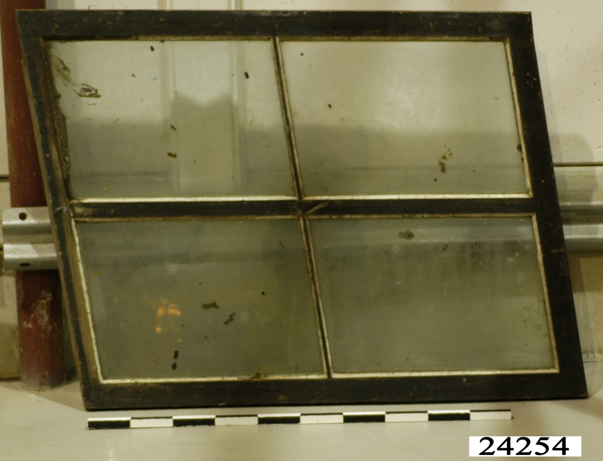 Spröjsat fönster med fyra glas inom snedvinklad ram av trä. Ramen har svartmålad utsida och gråmålad insida. Vitt kitt runt glasrutorna.