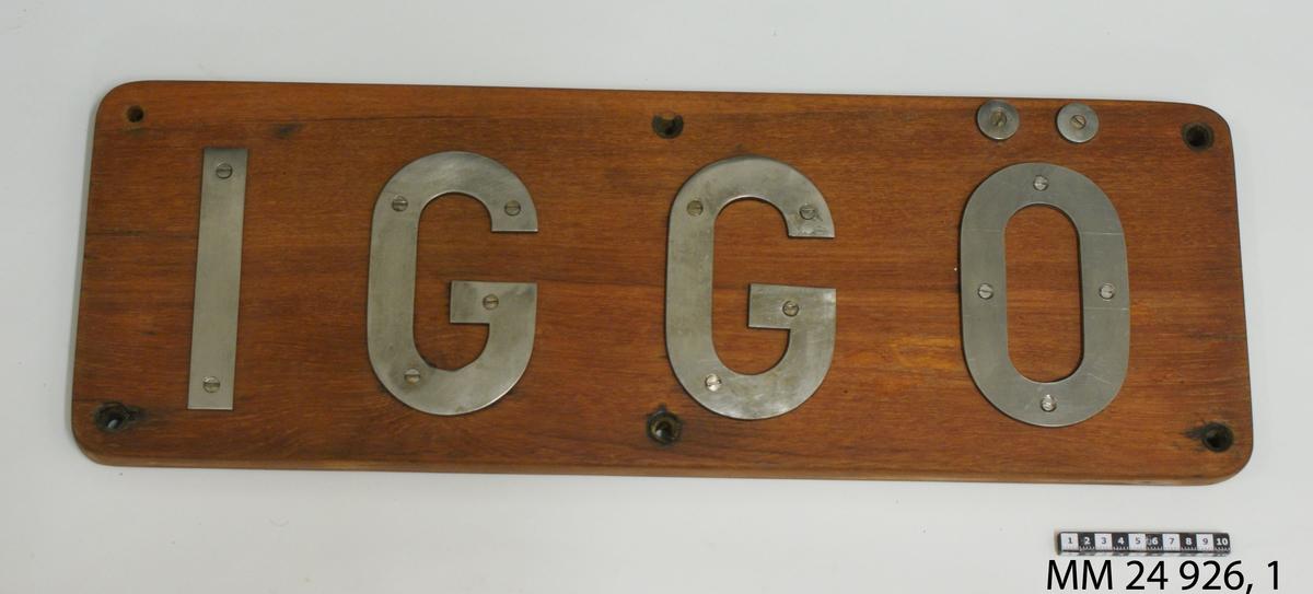 """Namnbräda av fernissat teak. Bokstäver av stål fastskruvade från framsidan, bildar namnet: """"Iggö""""."""