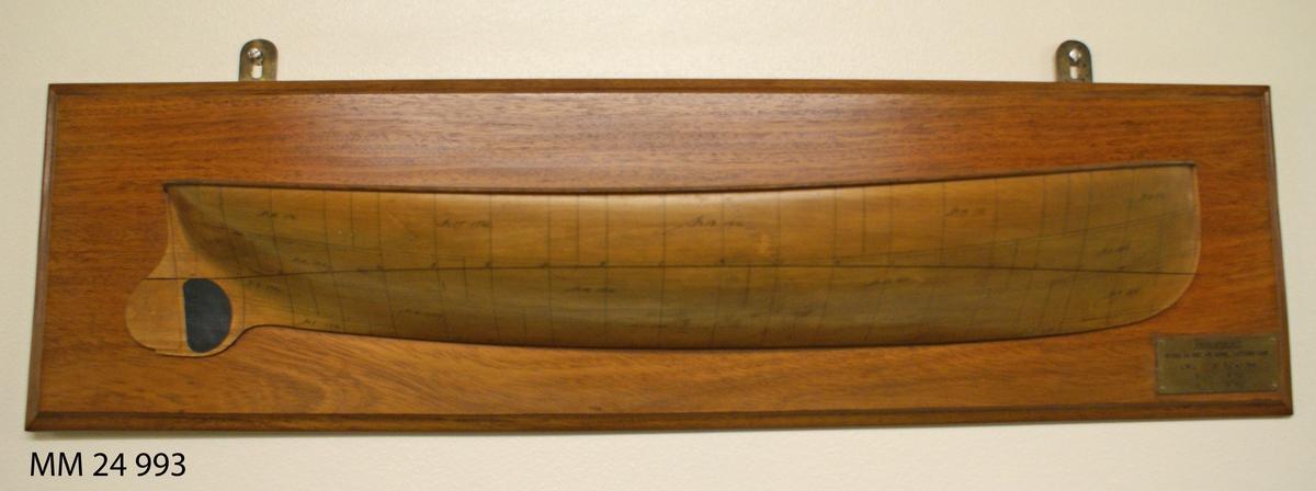 """Halvmodell av fernissat trä föreställande Ångslupen nr 1. Styrbordssida, på skrovet finns plåtarna och deras numrering utmärkt med tunna svarta streck. Halvmodellen är fäst på fernissad träplatta. I nedre högra hörnet finns mässingsbricka med texten: """"Ångslupen nr 1, Byggd år 1887 vid Kungl. flottans varf"""", samt måttuppgifter."""