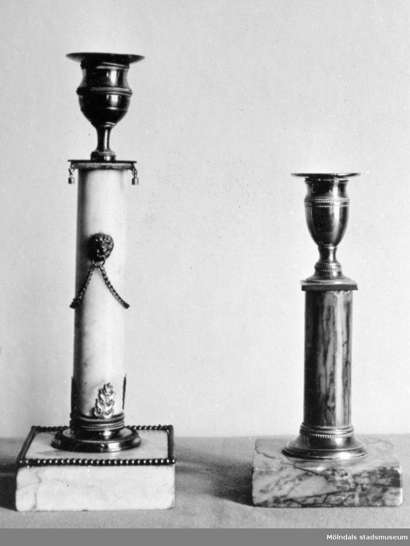 Två ljusstakar i marmor varav den vänstra är något högre samt ljusare. Båda har metallfattning för ljus samt marmorsockel. Gunnebo slott, 1930-tal.