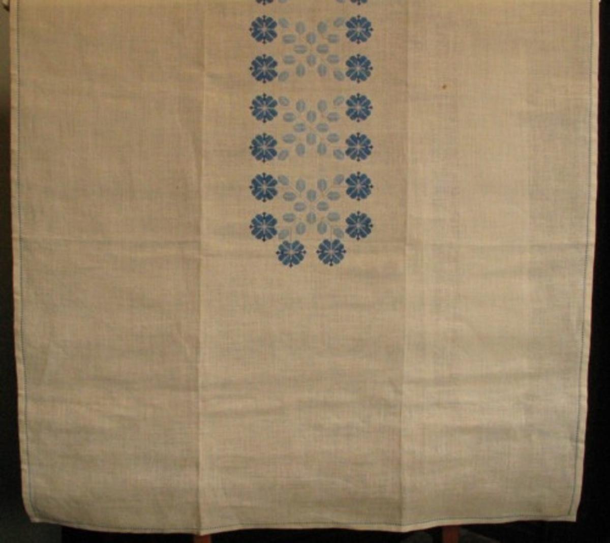 Broderad rektangulär stor duk, sydd på Skollinne II med Klippans HV 40/2 i 4 nyanser blått och grått. Finns även i rosa färgsättning. Mönstret av blå blommor och grå blad bildar en bård på mitten 18 x 95 cm. Duken är fållad med hålsöm.