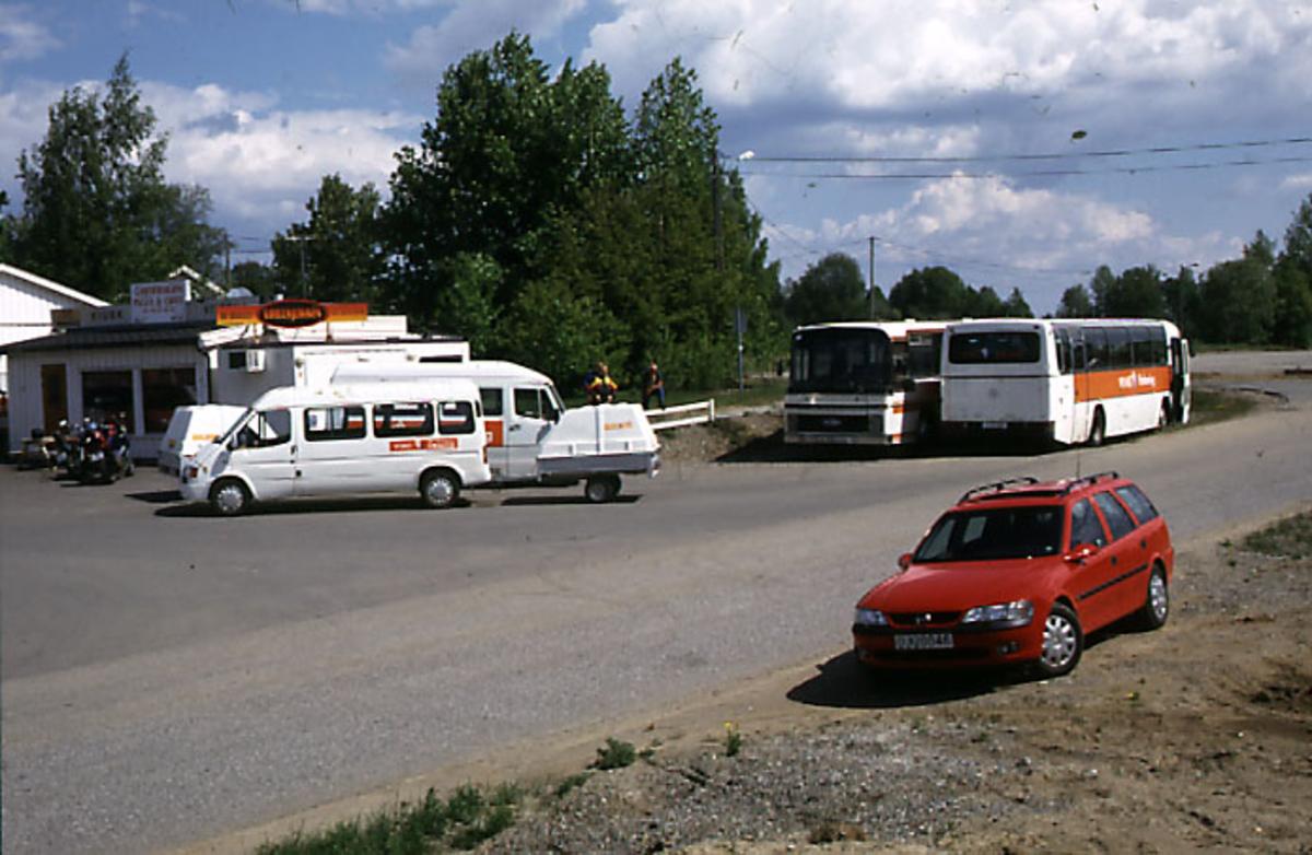 Lufthavn, 2 busser og 3 andre kjøretøyer parkert på parkeringsplass. 2 bygninger i bakgrunnen.