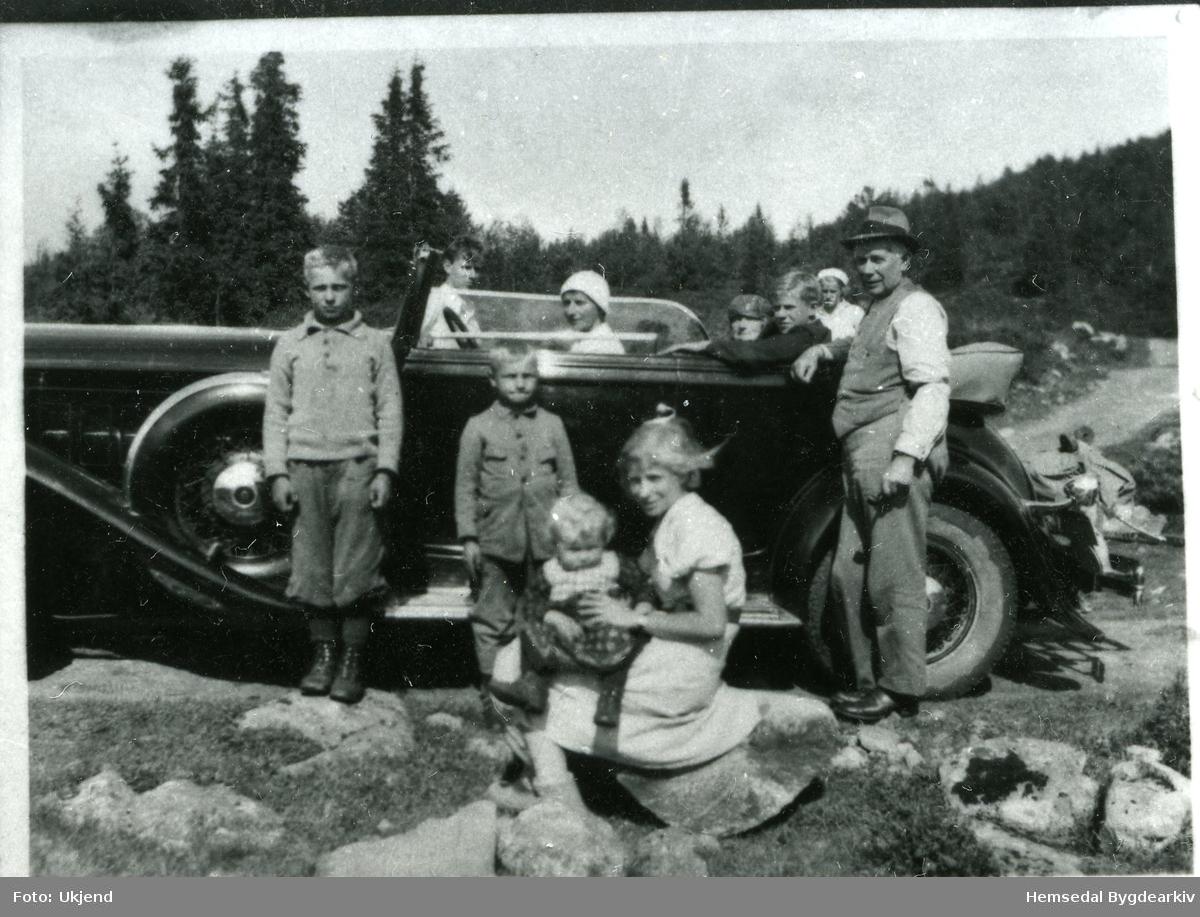 Byfolket som har hytta bak stølen, skal reisa attende til byen med drosje. Drosja tilhøyrde A/L Hemsedalbilane. Dei tre yngste ungane i Aalrust får vera med på biletet. Frå venstre: Lars (1927), Olav Magne (1930) og Margit Marie (1936). Biletet er teke i 1937.