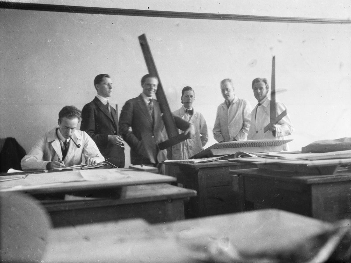 Gruppbild av sex unga män i en ritsal med vinkellinjaler och ritbord. David Helldén sittande längst till vänster. Arkitektskola Interiör
