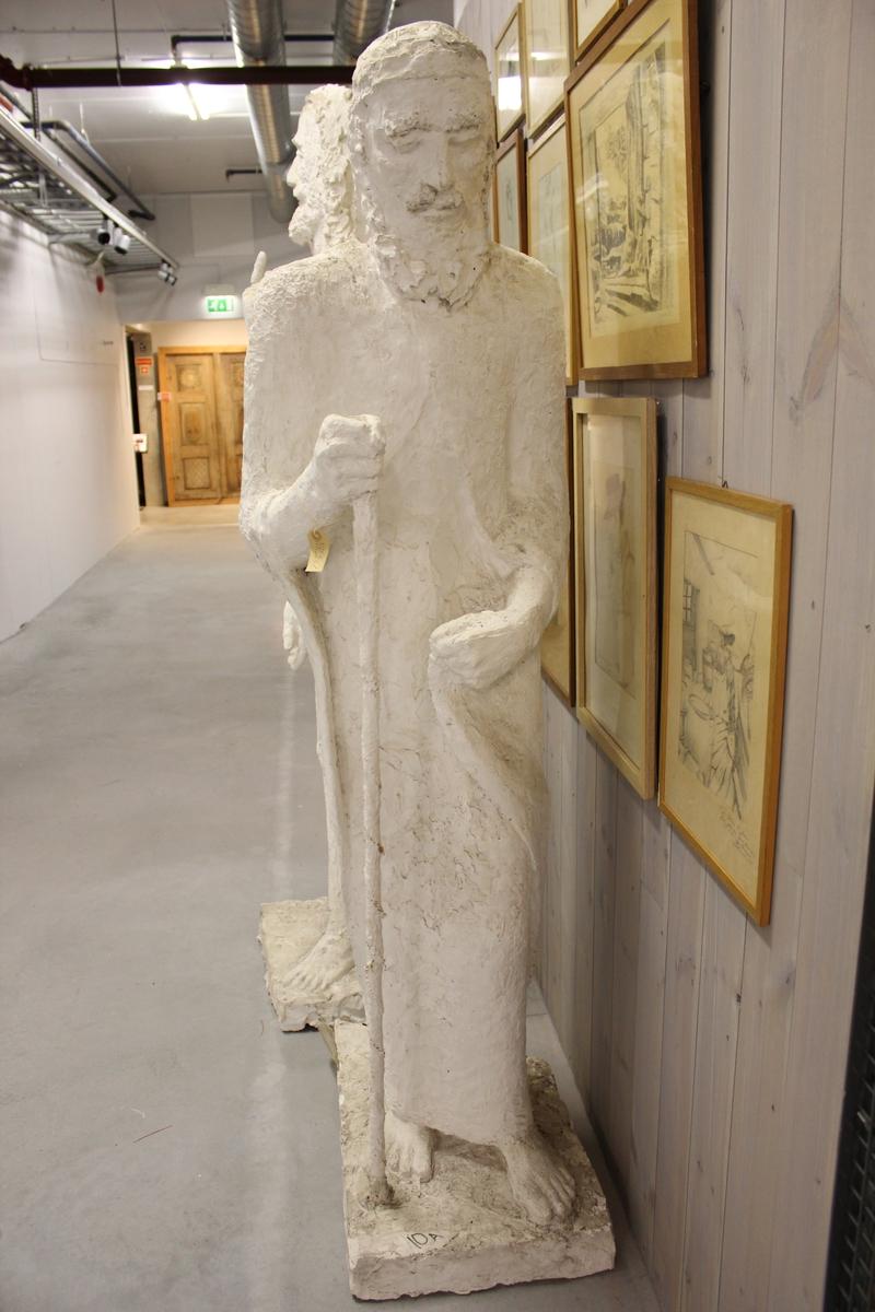 """Skulptur i gips av en mann i kjortel med stokk. Tittel """"Emmausvandrerne"""". Se også nr.262 og nr.263"""