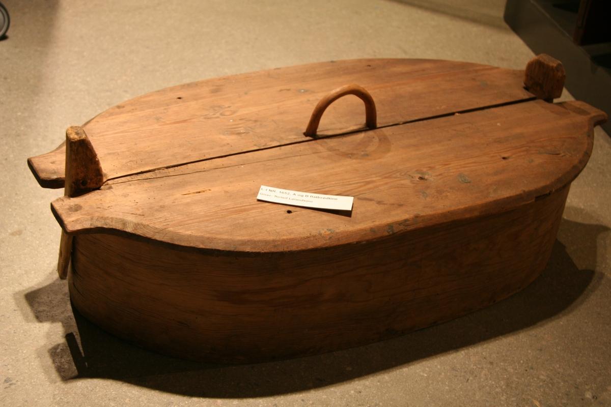 Flatbrødtine med lokk. Bunnen laget av to breie bord. I hver ende går fra bunnen og et stykke over kanten av tina to treklyper. Disse er det lokket blir festet i. Side stykket er laget av et tynt trestykke, som er ovalt formet og sydd sammen av to sømmer på enesiden og festet med spiker til bunnen. Lokket er ovalt og laget av to breie bord og festet sammen på innersiden av to små trelister tvers over. I hver ende går det ovale lokket over i en butt kant med innhukk, slik at lokket passer i klypene. Hantak på midten ovenpå. Tine: Tykkelse: 2 cm