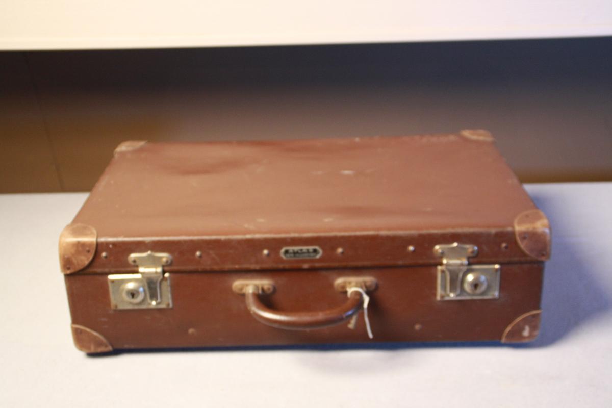 Brun koffert i vulkanfiber med lærforsterking på hjørnene og handtak. Metallknotter på bunnplata og metallåser. Varemerke ATLAS i metall festet på lokk ved handtak.