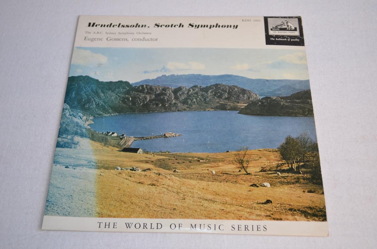 Grammofonplate med etui i papp. På pappetuiet er det bilete av ein gard ved ein fjord. Biletet er misfarga på venstre side framme.