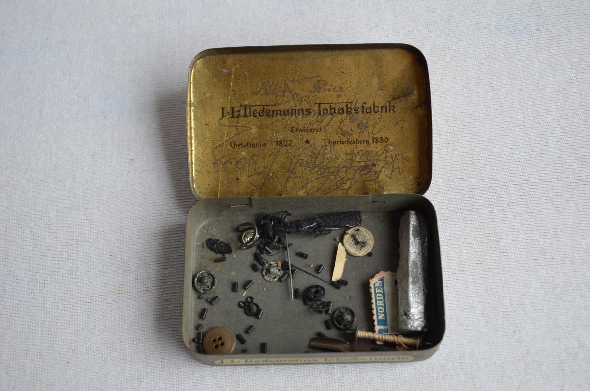 Blikkboks frå produsenten J.L. Tiedemanns Tobaksfabrik, av merket The Carter Mixture. Boksen har vore nytta til oppbevaring av sysaker og liknande. På innsida av loket har familen rissa inn namnet sitt.