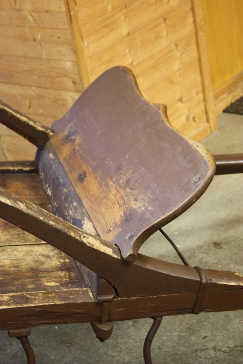 Jernskodde hjul på aksling utan fjøring. Sete med boga rygg, festa på åker til langskjekene. Dreia spiler i seterygg. Trebrett framme til vern mot sprut og bak til bagasje eller kusk. Stigbøyler av jern.