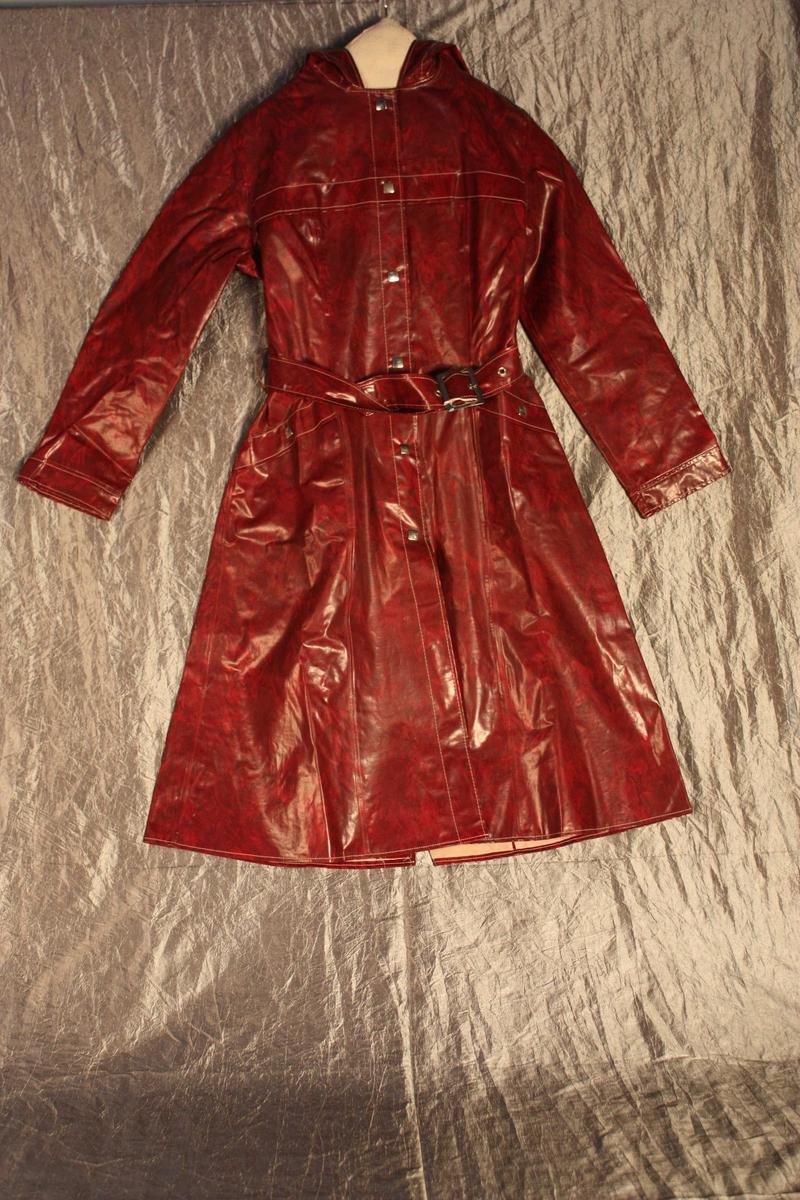 Form: Knelang frakk med hette, splitt med opp til livet bak, innsvinga i livet, belte med spenne. Knapping med seks trykknappar. Innvendige lommer med skrå linning utapå. fals berestykke.