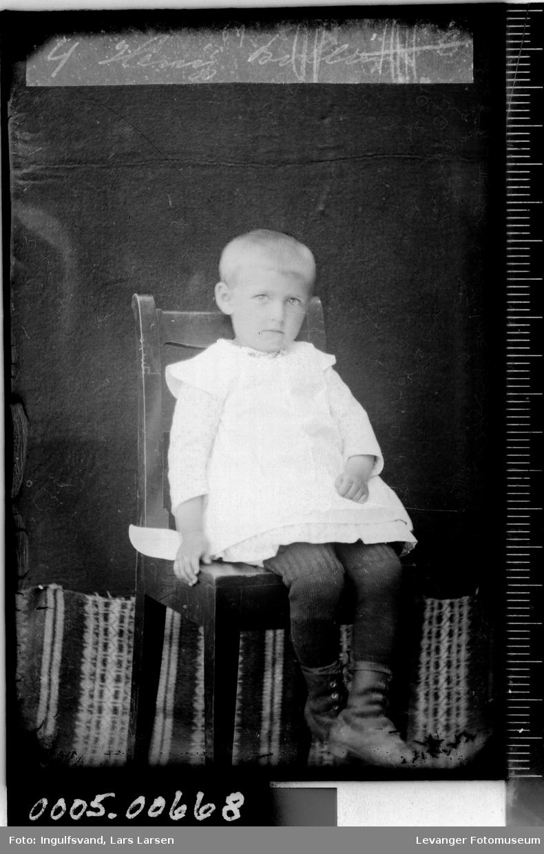 Portrett av gutt som sitter på en stol.