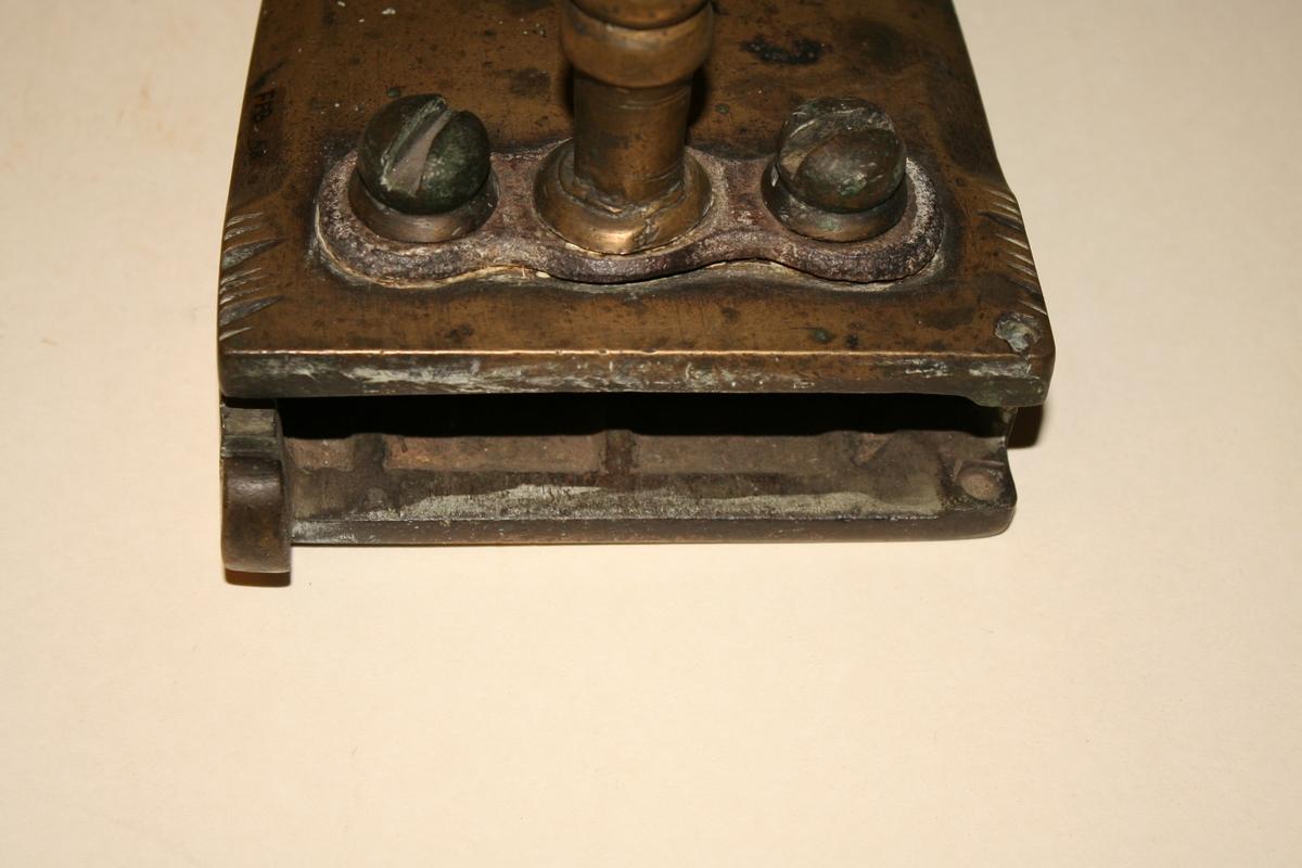 Kraftig strykejern i messing med glødestein. Håndtakholdere også i messing, dreid og profilert skrudd fast med kraftige messingskruer. Dreid horisontalt trehåndtak. I bakre end av jernet en rektangulær åpning (mangler dør) hvor det er lagt inn varmejern/ glødejern.