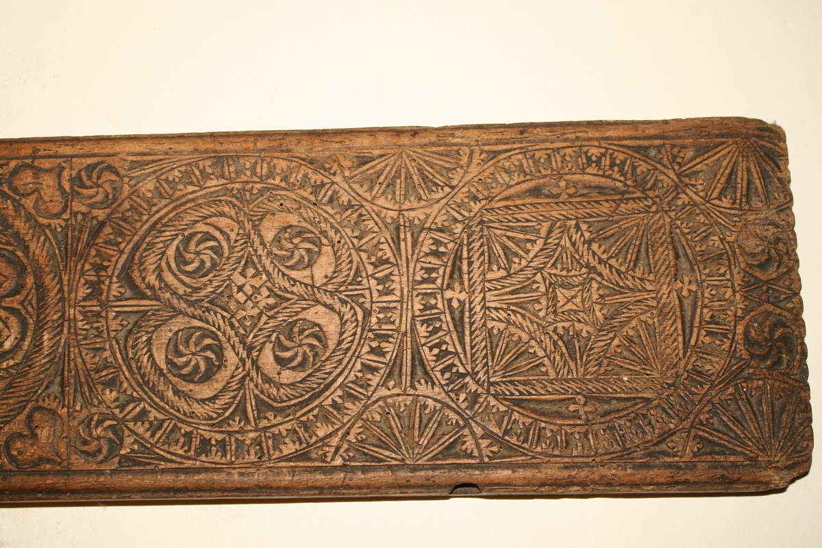 Rett, rektangulær trefjøl, i ene enden inntappet en utskåret trehest som håndtak. Rikt dekorert med karveskurd langs hele oversiden. Brukt sammen med sylindrisk trestokk til stryking av tekstiler.