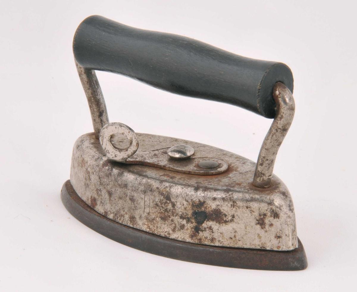 Lite strykejern  av jern. Trehandtak. Sjølve strykeflata kan takasta av ved å opne ein lås på øvre del av strykejernet.