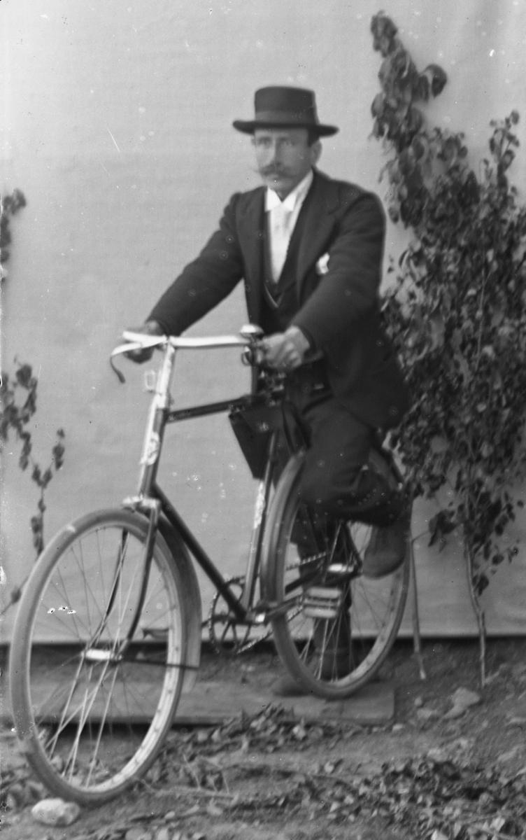 Dresskledd mann på sykkel med lerretbakgrunn.