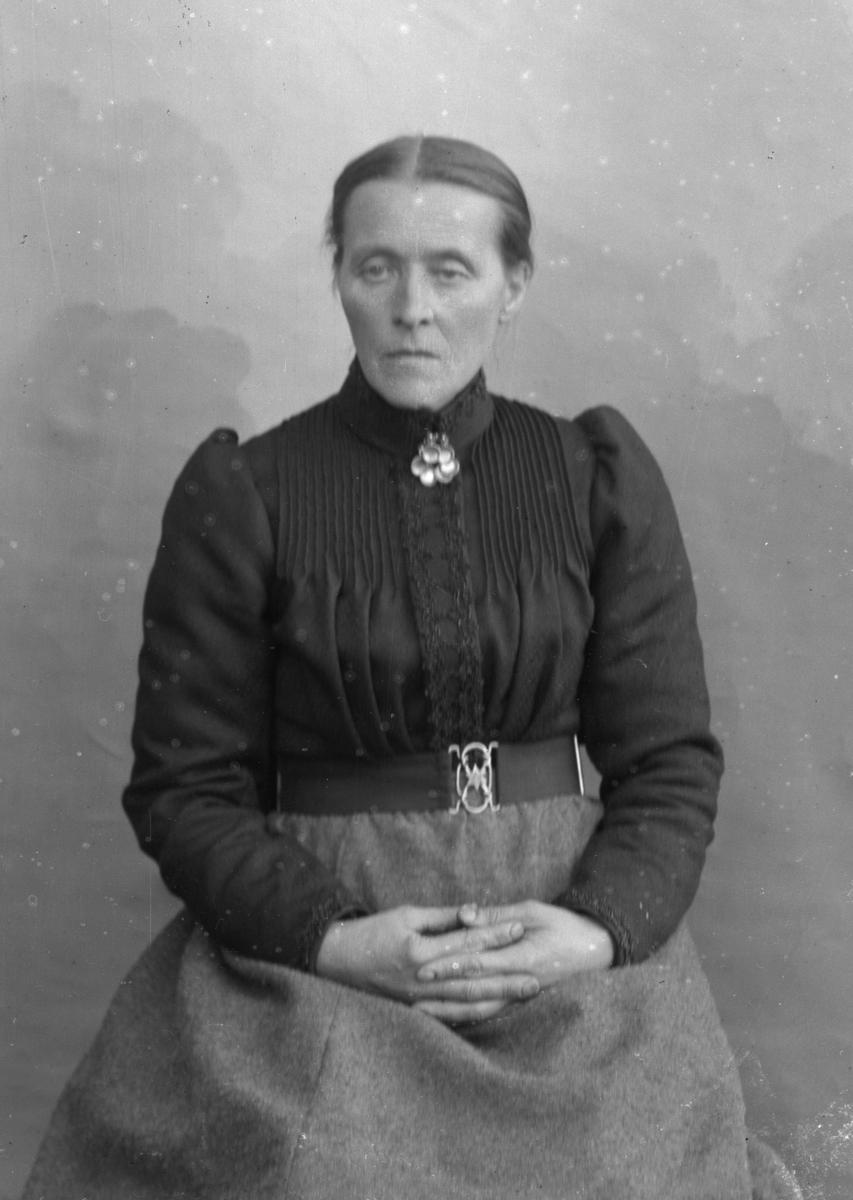 Sittende kvinne foran lerretbakgrunn