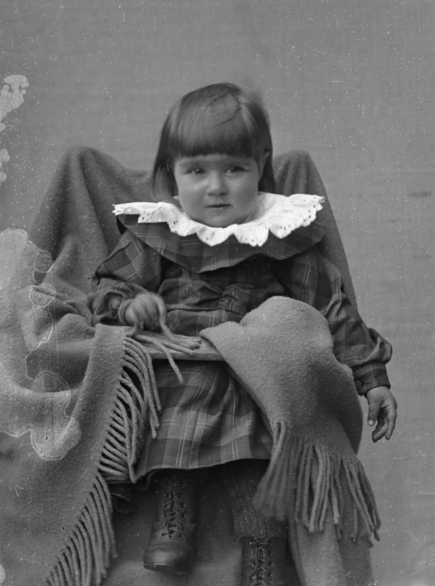 Jente i rutete kjole, sittende i barnestol med pledd, lerretbakgrunn