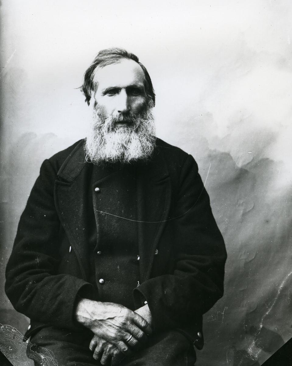 Eldre mann i halvfigur, sittende foran lerret