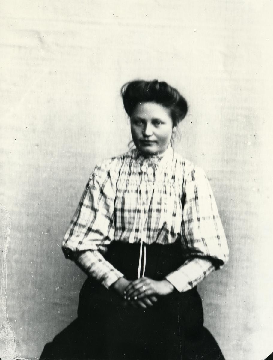 Kvinne kledd i rutete skjorte, sittende foran lerret